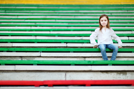assigned: Cute little girl sitting on a stadium seat Stock Photo