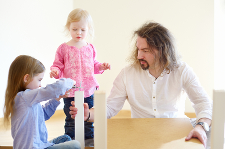 Happy father and his two daughters assembling a table together