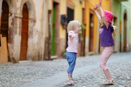 niños bailando: Dos pequeñas hermanas lindas que se divierten al aire libre
