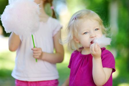 algodon de azucar: Hermanitas adorables comiendo algodón de azúcar al aire libre en verano Foto de archivo