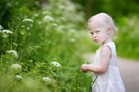 sad cute baby: Portrait of a very angry little girl outdoors Stock Photo