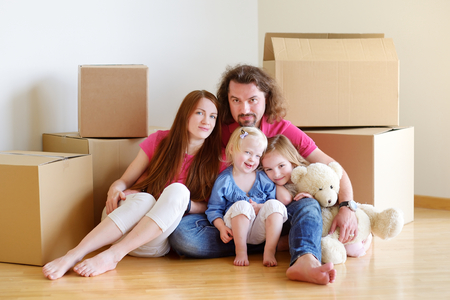 Happy young family sitting on a floor in their new home photo