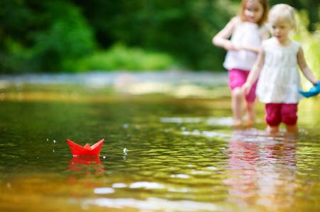 Dos pequeñas hermanas adorables que juegan con los barcos de papel en un río