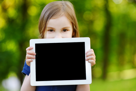 pad: Happy little girl holding tablet PC outdoors in summer park on beautiful sunny day