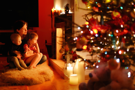 fireplace family: Young mother and her daughters by a fireplace on Christmas
