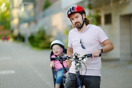 enfant banc: Young father and his cute little toddler daughter in a child seat getting ready to ride a bicycle