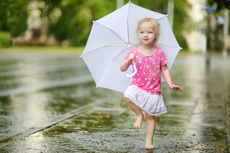 little girl barefoot: Cute little toddler girl standing in a puddle holding umbrella on a rainy summer day Stock Photo