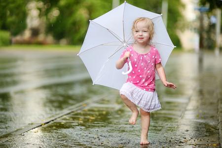 lluvia paraguas: Niña linda del niño de pie en un paraguas que sostiene charco en un día de verano lluviosa