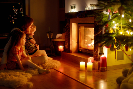 christmas room: Young mother and her two little daughters sitting by a fireplace in a cozy dark living room on Christmas eve
