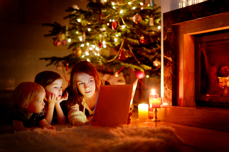 Joven madre y sus dos pequeñas hijas que leen un libro por un árbol de Navidad en la acogedora sala de estar en invierno