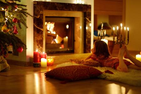 camino natale: Felice bambina che da un camino in un accogliente soggiorno buio alla vigilia di Natale