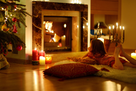 living room design: Happy little girl laying by a fireplace in a cozy dark living room on Christmas eve