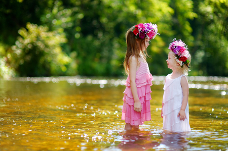 Two adorable little sisters wearing flower crowns by a river on warm and sunny summer day photo