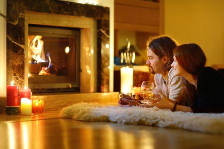 camino natale: Coppia felice con bevande da parte di un camino in un accogliente soggiorno buio alla vigilia di Natale