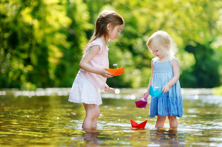 Two adorable little sisters playing with paper boats by a river on warm and sunny summer day photo