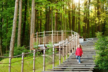down the stairs: Adorable niña caminando por las escaleras en el parque de verano en el hermoso día soleado