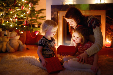 Young mother and her two little daughters opening a magical Christmas gift by a Christmas tree in cozy living room in winter Foto de archivo