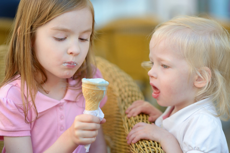 Two adorable little sisters eating an ice cream in outdoor cafe on beautiful summer day photo