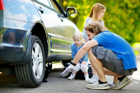 problemas familiares: Padre joven y sus dos hijas que cambian una rueda de coche al aire libre en el hermoso d�a de verano