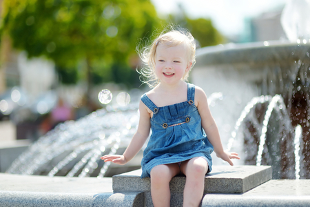 sitting on the ground: Cute little toddler girl playing with a city fountain on hot and sunny summer day