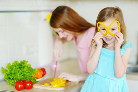 niños sanos: Mother and daughter cooking dinner in a kitchen