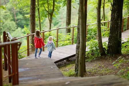 down stairs: Dos pequeñas hermanas que caminan por las escaleras en el parque de verano en el hermoso día soleado