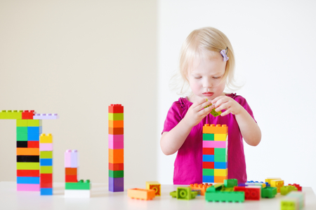 building bricks: Cute little toddler girl playing with colorful plastic blocks at home Stock Photo