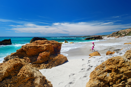 Cute little girl playing on a beautiful sandy beach on Sardinia photo