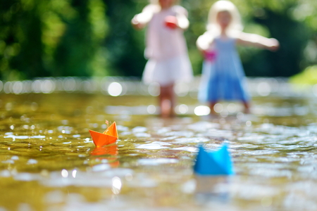 small paper: Two little sisters playing with paper boats by a river on warm and sunny summer day Stock Photo