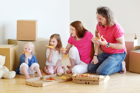 Happy young family sitting on a floor and eating pizza in their new home photo