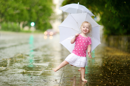Cute little toddler girl standing in a puddle holding umbrella on a rainy summer day Standard-Bild