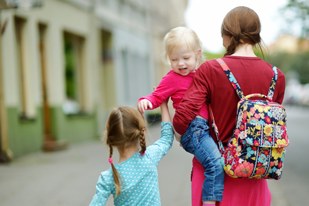 cradling: Young mother and her two cute daughters walking down the street on a summer day