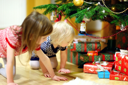 christmas baubles: Two adorable little sisters looking for gifts under a Christmas tree on Christmas eve at home