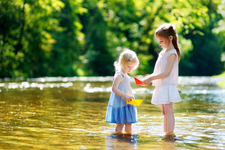 Two adorable little sisters playing with paper boats by a river on warm and sunny summer day Reklamní fotografie