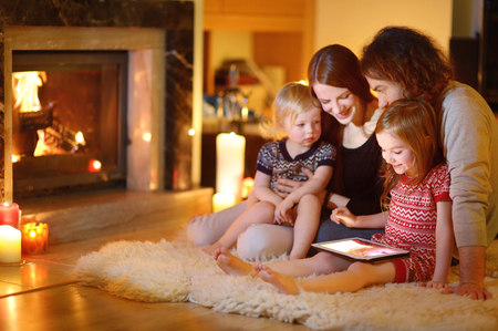 living room: Happy young family using a tablet pc at home by a fireplace in warm and cozy living room on winter day