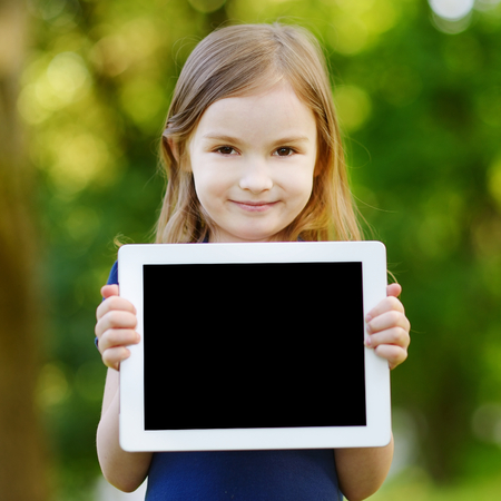 black kid: Happy little girl holding tablet PC outdoors in summer park on beautiful sunny day