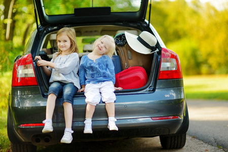 road vehicle: Two adorable little sisters sitting in a car just before leaving for a car vacation with their parents Stock Photo