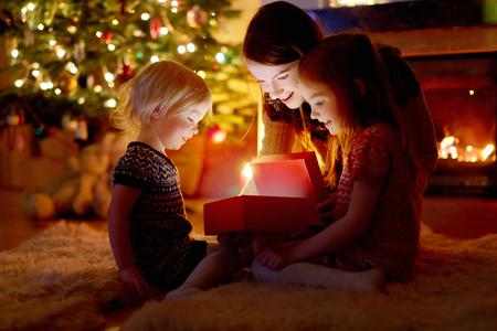magia: Joven madre y sus dos pequeñas hijas abren un regalo mágico de la Navidad por un árbol de Navidad en la acogedora sala de estar en invierno