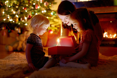 baby open present: Young mother and her two little daughters opening a magical Christmas gift by a Christmas tree in cozy living room in winter Stock Photo