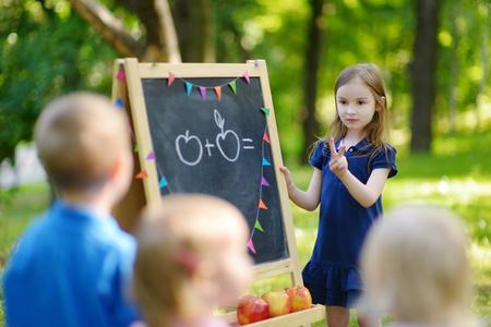 Niña adorable que juega un profesor de pie junto a una pizarra delante de sus pequeños estudiantes