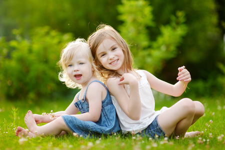 Two cute little sisters having fun while sitting on the grass on a sunny summer day photo