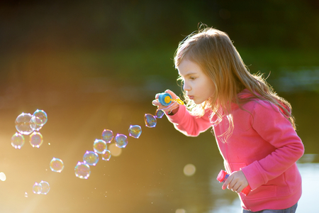 burbujas de jabon: La niña encantadora soplando pompas de jabón divertidos en una puesta de sol al aire libre Foto de archivo