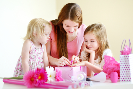 three wishes: Young mother and her two little daughters wrapping a gift with pink wrapping paper