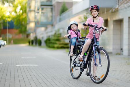 enfant banc: Jeune maman et son mignon petit b�b� fille dans un si�ge d'enfant se pr�pare � monter � bicyclette