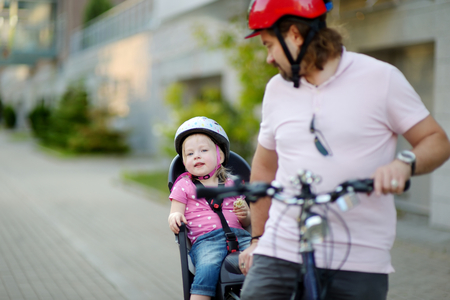 helmet seat: Young father and his cute little toddler daughter in a child seat getting ready to ride a bicycle