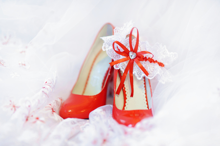 garter: Elegant bright red bridal shoes and a white garter Stock Photo