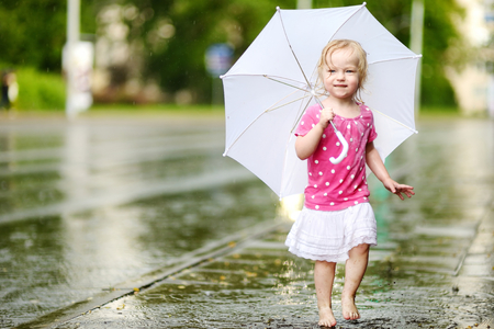 Cute little toddler girl standing in a puddle holding umbrella on a rainy summer day Фото со стока