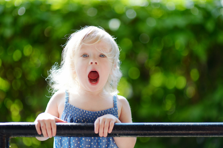 mouth smile: Adorable toddler girl screaming, singing and making funny faces outdoors at summer