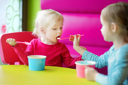 Two cute little sisters eating ice cream together in a colorful outdoor cafe photo