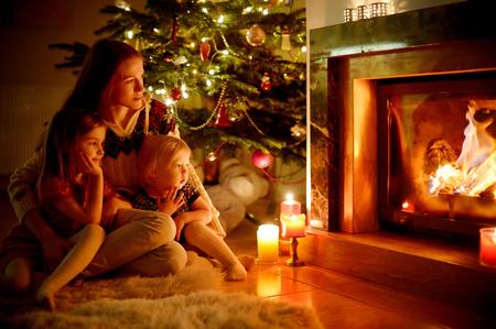 Jonge moeder en haar twee kleine dochters zitten door een open haard in een gezellige donkere woonkamer op kerstavond